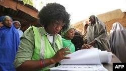 Giới chức bầu cử kiểm tra danh sách cử tri tại một phòng phiếu ở Daura, Nigeria, ngày 16 tháng 4, 2011