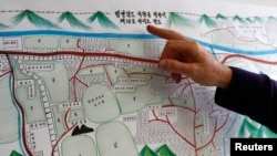 A United Nations Human Rights staff points to the title of a drawing describing North Korean labour camp no 18, a gift by survivor Kim Hye Sook.