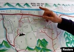 2014년 스위스 제네바에서 북한 수용소 감독원 출신 탈북자 김혜숙 씨가 그린 정치범 수용소 그림을 유엔 관계자가 설명하고 있다.