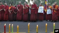 Tibetan exile monks stand during a candlelit vigil in New Delhi, India, to express solidarity with the plight of the Tibetan people.