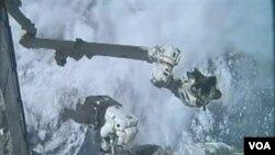Dua astronot Atlantis menggunakan sebuah tangan robot untuk melepaskan wadah pengangkut barang ISS (12/7).