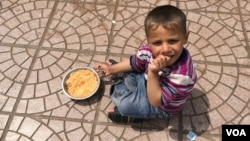 Young Iraqi boy eating rice with tomato sauce. (S. Behn/VOA)