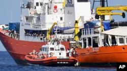 """FILE - An Italian Coast Guard boat approaches the French NGO """"SOS Mediterranee"""" Aquarius ship as migrants are being transferred, in the Mediterranean Sea, June 12, 2018."""
