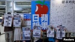 Para anggota staf koran independen Hong Kong, Apple Daily dan penerbitnya, Next Digital, berfoto dengan edisi terakhir koran itu di kantor pusatnya, di Hong Kong, China, 24 Juni 2021. (Foto: Tyrone Siu/Reuters)
