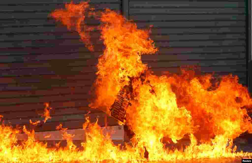 Polícia anti-motim rodeado de chamas na Praça Syntagma, em Atenas
