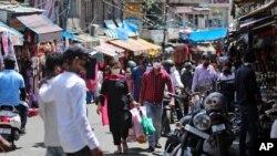 Warga India mengenakan masker saat berbelanja di sebuah pasar di Jammu, India, Minggu, 5 Juli 2020.(AP Photo/Channi Anand).
