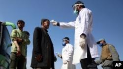 Arhiva - Zdravstveni radnici mere telesnu temperaturu avganistanskim putnicima, u okviru napora da se spreči širenje Kovida 19, na ulazu u Kabul kroz Zapadnu kapiju, u Pagman distriktu, Avganistan, 22. marta 2020.