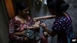 Медик делает прививку от полиомиелита ребенку. Исламабад. Пакистан. 17 июля 2012 г.