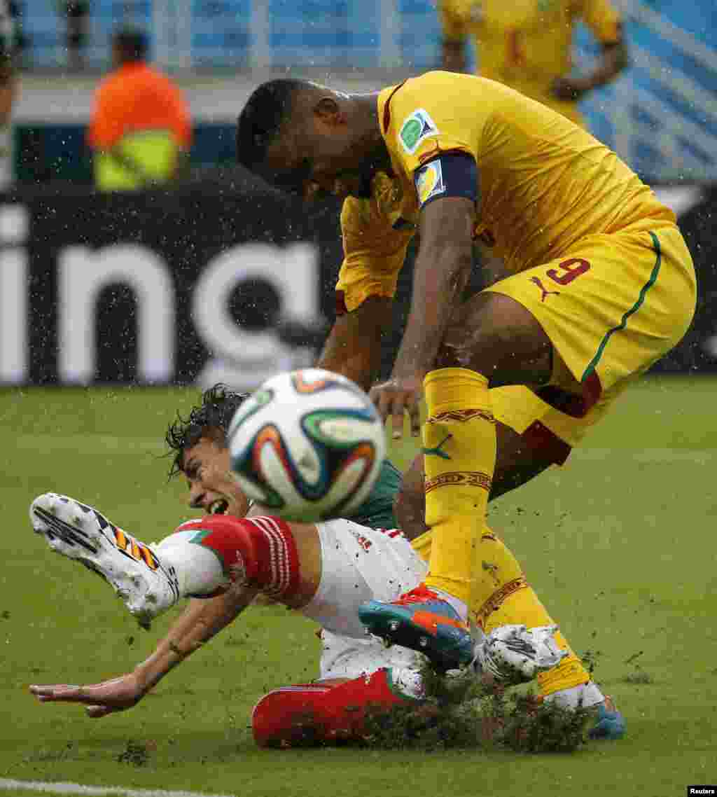 Mexico's Hector Moreno (on the ground) fights for the ball with Cameroon's Samuel Eto'o during their 2014 World Cup Group A soccer match at the Dunas arena, in Natal June 13, 2014.