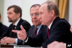 Russian President Vladimir Putin, accompanied by Russian Foreign Minister Sergei Lavrov, second from right, speaks during a meeting with Secretary of State John Kerry at the Kremlin in Moscow, Russia, Thursday, March 24, 2016.