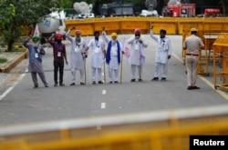 Petani meneriakkan slogan-slogan dalam aksi protes menentang undang-undang pertanian, di dekat gedung parlemen di New Delhi, India, 22 Juli 2021. (REUTERS/Adnan Abidi)