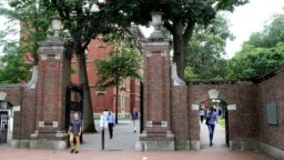 FILE - Para pejalan kaki melewati gerbang Harvard Yard di Universitas Harvard, Cambridge, Massachusetts.