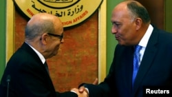 French Foreign Minister Jean-Yves Le Drian shakes hands with Egyptian Foreign Minister Sameh Shoukry (R) after their joint news conference in Cairo, Egypt, June 8, 2017.