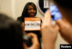 FILE - A woman poses for photos while holding a placard with her thoughts on health care at the White House Youth Summit on the Affordable Care Act in Washington, Dec. 4, 2013.