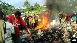 Bystanders watch as a woman accused of witchcraft is burned alive in the Western Highlands provincial capital of Mount Hagen in Papua New Guinea, February 6, 2013.