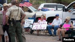 FILE - Thelma and Don Christie, center, of Tucson demonstrate against the arrival of undocumented immigrants in Oracle, Arizona, July 15, 2014.