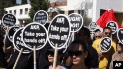 Turkish Cypriot protesters hold placards at a demonstration in northern Nicosia, March 2, 2011