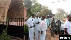 Health officials stand outside La Terrasse restaurant where militants killed five people, including a French citizen and a Belgian citizen, in a gun attack in Bamako, March 7, 2015.
