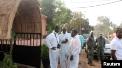 FILE - Health officials stand outside La Terrasse restaurant in Bamako, where five people were killed in a militant attack, March 7, 2015.