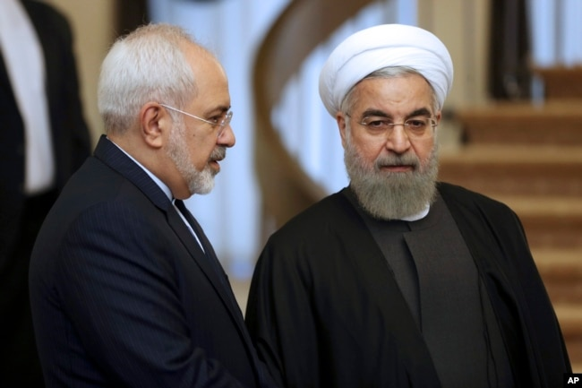 FILE - Iranian President Hassan Rouhani, right, listens to Foreign Minister Mohammad Javad Zarif before a meeting in Tehran, Iran, Nov. 24, 2015.