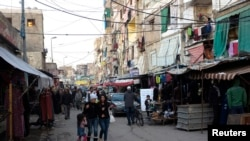 FILE - Shoppers walk along the main street of the Shatila Palestinian refugee camp on the outskirts of Beirut.