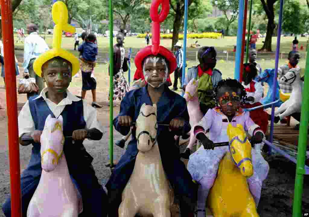 Kenyan children ride a carousel as families gather to celebrate the new year at Uhuru Park, Nairobi, Kenya, January 1, 2013.