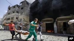 Petugas medis Palestina membawa korban sambil berlari melewati gedung yang terbakar di Shijaiyah, Gaza City di Jalur Gaza utara, Minggu, 20 Juli 2014.