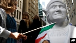 Isabella Nordstrom waves an Italian flag near a large statue of Christopher Columbus before the Columbus Day Parade in New York on Oct. 14, 2013. (AP Photo/Seth Wenig)