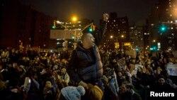 一名抗議者在紐約曼哈頓的集會中舉臂抗議之前發生兩宗白人警員殺死未帶武器的黑人卻被免予起訴的個案。