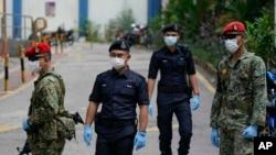 马来西亚军人和警察2020年3月31日在当局宣布居家令之后在吉隆坡一公寓外。居家令将延伸到4月15日。