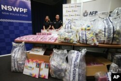 FILE - Australia Methylamphetamine: Officers stand by a display of confiscated drugs in Sydney, Monday, Jan. 15, 2016.