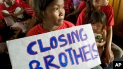 "A Cambodian sex worker, center, holds a banner read ""Closing Brothels"" in a conference room in Phnom Penh, file photo."