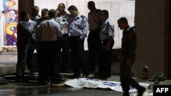 Israeli policemen stand next to the body of a suspected Palestinian attacker, who opened fire on people at a bus station in the southern Israeli city of Beersheva, Oct. 19, 2015.