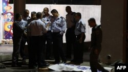 FILE - Israeli policemen stand next to the body of a suspected Palestinian attacker, who opened fire on people at a bus station in the southern Israeli city of Beersheba, Oct. 19, 2015.