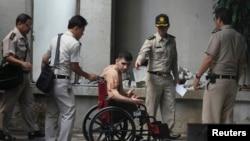 Giám thị trại giam đẩy xe lăn đưa nghi can Saeid Moradi đến tòa án hình sự tại Bangkok.