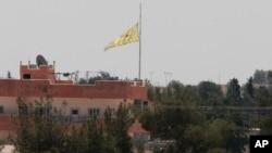 ຮູບພາບນີ້ ຖ່າຍຈາກຟາກເຂດຊາຍແດນ ໃນເມືອງ Akcakale ຢູ່ທາງພາກຕາເວັນອອກສຽງໃຕ້ ຂອງເທີກີ ລະຫວ່າງ ຊີເຣຍ ຊຶ່ງແນມເຫັນທຸງ ຂອງໜ່ວຍປົກປ້ອງ ປະຊາຊົນຊາວເຄີດ ຫຼື YPG, ພັດປິວ ຢູ່ໃນເມືອງ Tal Abyad ປະເທດຊີເຣຍ, ວັນທີ 16 ມີຖຸນາ 2015.