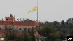 FILE - In this photo taken from the Turkish side of the border between Turkey and Syria, in Akcakale, southeastern Turkey, a flag of the Kurdish People's Protection Units, or YPG, flies over the town of Tal Abyad, Syria, June 16, 2015.