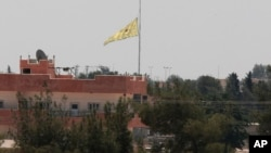 Pasukan Kurdi mengibarkan bendera di sebuah gedung di Tal Abyad, Suriah hari Selasa (16/6).