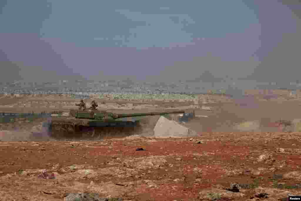 Syrian army tanks loyal to President Bashar al-Assad advance toward the Handarat camp, near Aleppo, May 21, 2014.