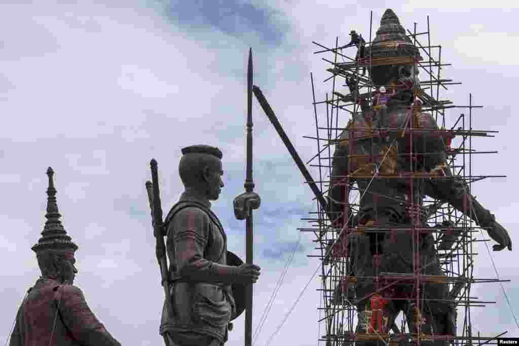Công nhân làm việc trên những bức tượng đồng khổng lồ của Quốc vương Ram Khamhaeng (phải) tại Công viên Ratchapakdi ở Hua Hin, tỉnh Prachuap Khiri Khan, Thái Lan. Công viên đang được quân đội Thái Lan xây dựng để tôn vinh những quốc vương thời xưa của Thái Lan trên một khu đất của quân đội gần Dinh Klai Kangwon. Dự án ước tính trị giá khoảng 19,9 triệu đồng, theo truyền thông địa phương.