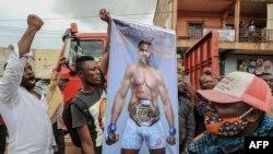 Une banderole à l'effigie du Camerounais Francis Ngannou, champion du monde des arts martiaux mixtes poids lourds (MMA), alors qu'il conduisait dans les rues de Bafoussam, au Cameroun, le 1er mai 2021, pour présenter sa ceinture de championnat.