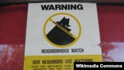 Tanda peringatan 'Siskamling' di kawasan permukiman di Amerika. Orang yang bertingkah laku mencurigakan bisa dilaporkan ke polisi.