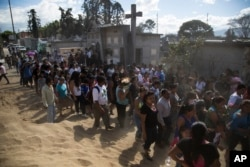 People accompany the burial of 14-year-old Madelyn Patricia Hernandez Hernandez, a girl who died in a fire at the Virgin of the Assumption Safe Home, at the Guatemala City's cemetery, March 10, 2017.