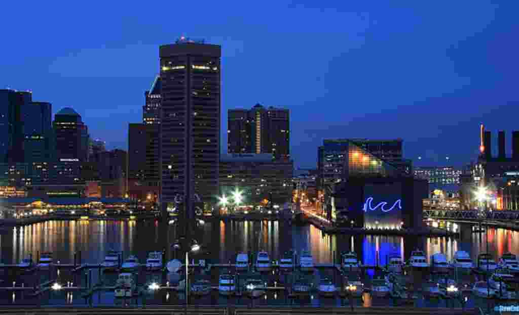 "Baltimore's downtown showplace, the Inner Harbor. The neon ""wave""design marks the National Aquarium, one of the major attractions. The tall building to its left is Baltimore's pentagonal shaped World Trade Center. © Steve Ember"