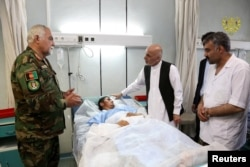 Afghanistan's President Ashraf Ghani visits a victim wounded in April 21's attack on an army headquarters, in Mazar-i-Sharif, April 22, 2017.