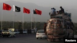 People sit on top of a bus as they go past flags of Pakistan and China that are displayed along a road.