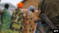 Des femmes et un homme armé à Aveba, dans le sud de l'Ituri, RDC, 30 juillet 2006.