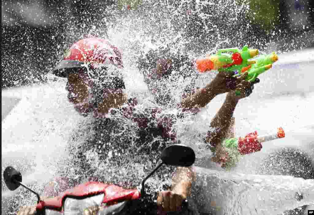 Orang-orang mengendarai sepeda motor sementara seorang anak lelaki melemparkan air ke arah mereka dalam perayaan Tahun Baru Thailand atau festival air Songkran di Bangkok.