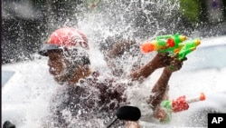FILE - People riding on a motorbike react as a boy splashes water on them during traditional Thai New Year celebrations or Songkran water festival in Bangkok, April 13, 2015.