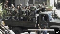 Des soldats syriens laissant le quartier de Saqba, à Damas, le 14 août 2011